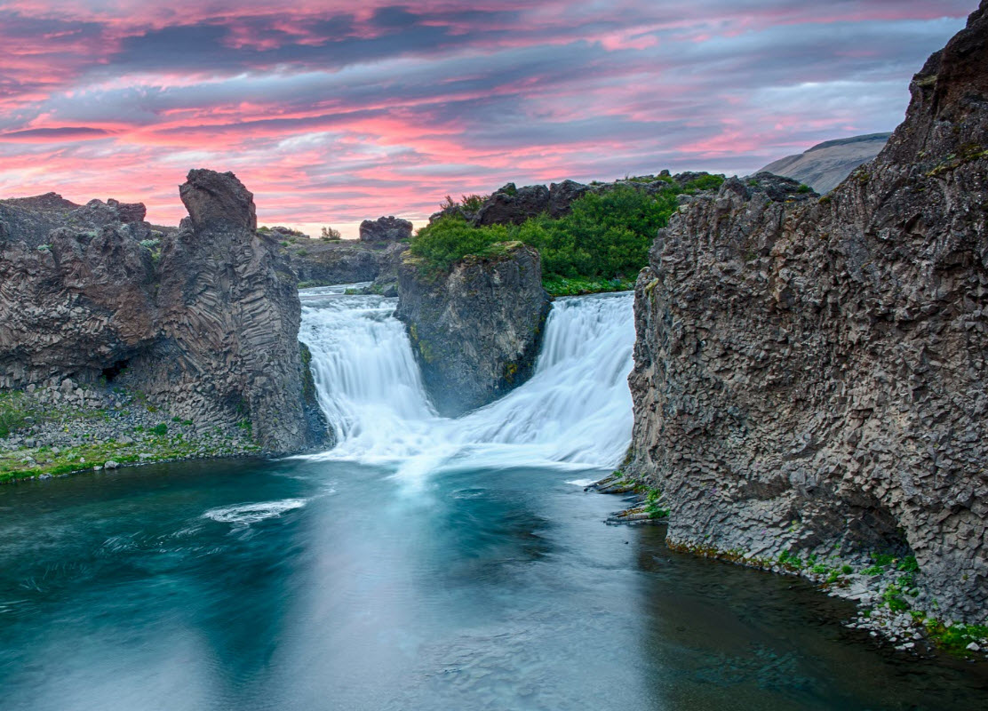 Midnight sunset by the double waterfall Hjalparfoss in Iceland