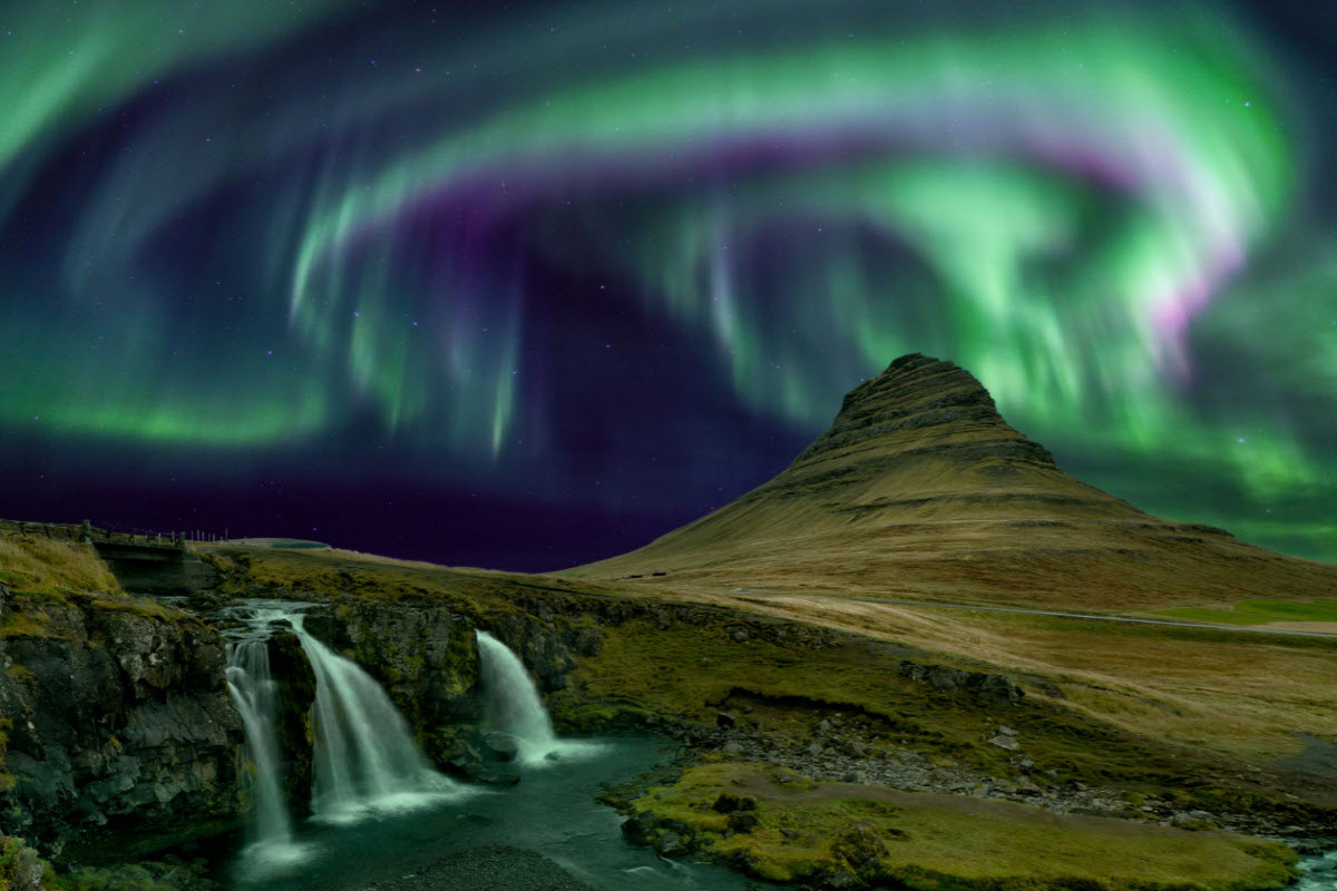 The Northern Lights dancing around above Kirkjufell Mountain