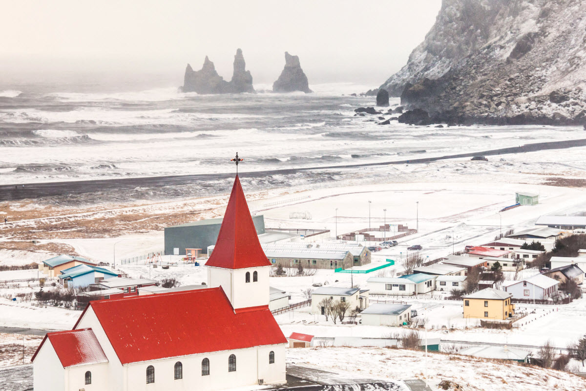 The town Vík during winter with the basalt sea stacks Reynisdrangar in the background