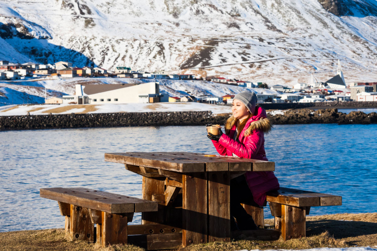 Enjoying a picnic with a view over the town Olafsvik during winter in Iceland