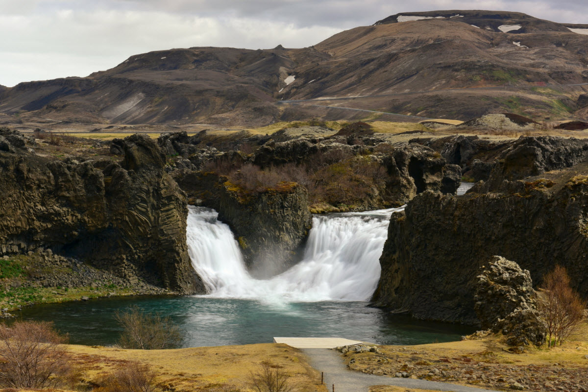 Hjalparfoss waterfall is located in a lava field north of the volcano Hekla