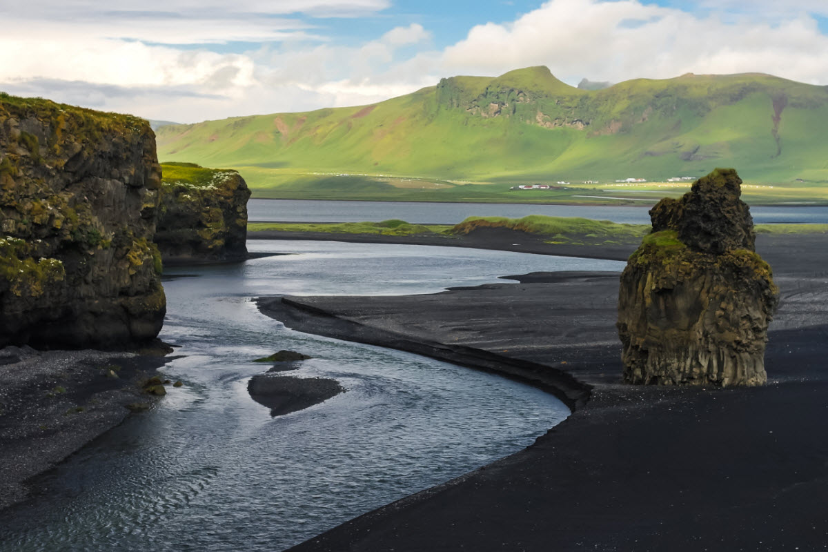 The landscape from Dyrholey cape over the black volcanic beach in South Iceland
