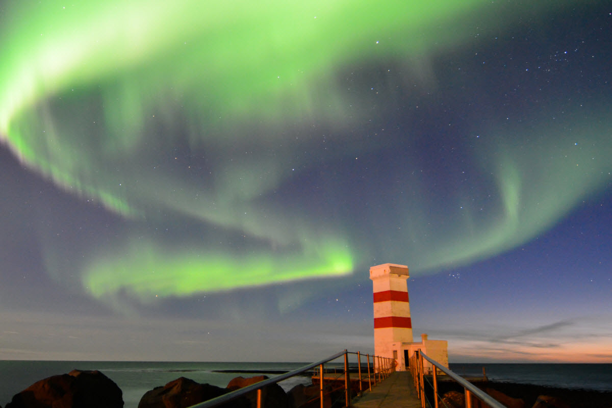 The Northern Lights dancing above the lighthouse in Gardur town, Iceland